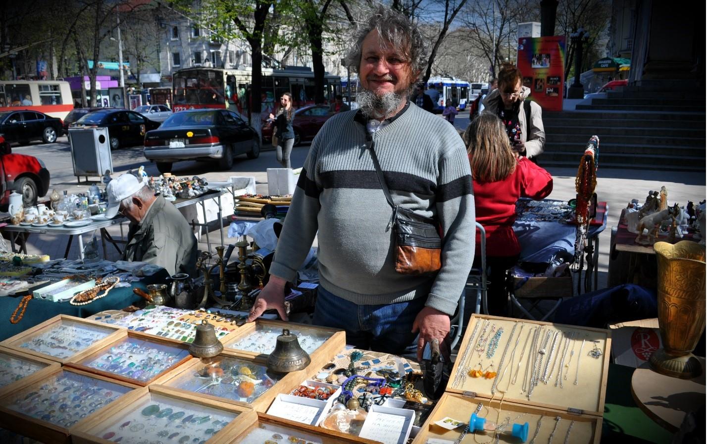 Один из продавцов с удовольствием рассказывает о предметах, находящихся на прилавке