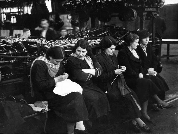 Auto workers knitting to pass time during sitdown strike at Citroen plant. Location:France Date taken: 1937 Photographer:Kitrosser