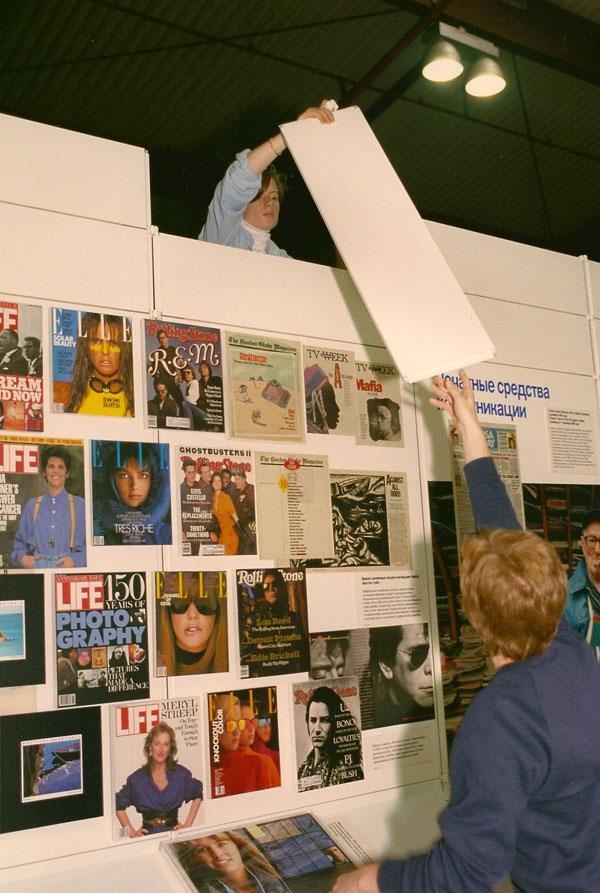 Moscow, 1989- Guides Karen Olson and Diane Reinsch assemble wall of American magazines at Design USA. [Photo by Amanda Merullo, 1989]