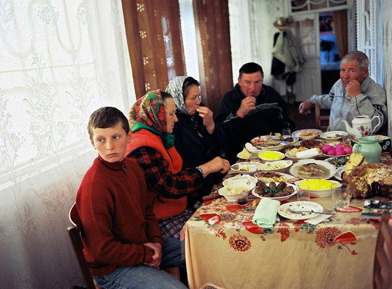 8. 15-летний Славик с бабушкой и дедушкой и их соседями на Пасху. Его мать уехала в Италию в 2004 году – работать горничной.