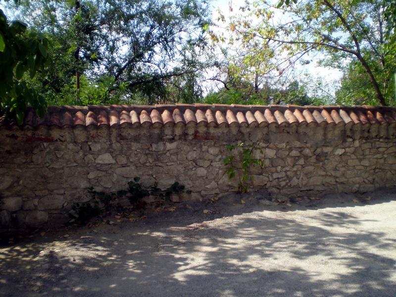 Забор слева от входа, за ним - глубокий овраг.