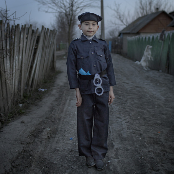 Хью младший в костюме полицейского играет рядом с домом, в маленьком молдавском селе Баронча. Фото Asa Sjöström