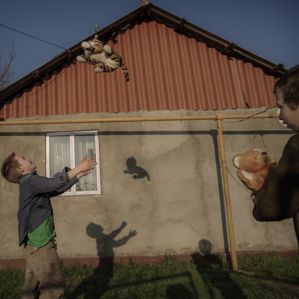Игорь и его брат близнец играют с мягкими игрушками в свой день рождения. Их родители погибли находясь на заработках в Москве. Фото Asa Sjöström