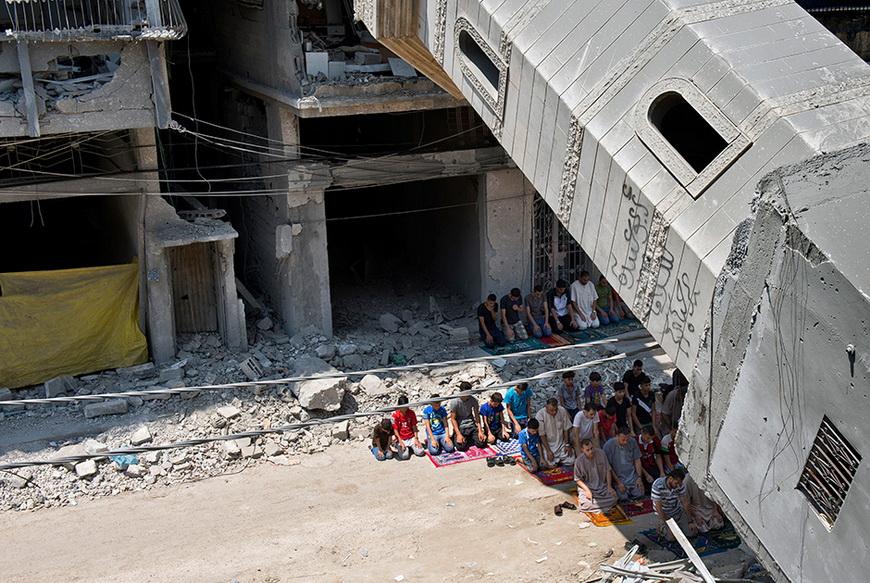 Палестинцы молятся в тени минарета, разрушенного в результате авиаударов израильтян. 15 августа, сектор Газа. Фото: Roberto Schmidt / AFP
