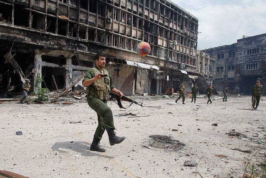 Солдаты президентских войск Башара Асада играют в футбол в городе Хомс. Сирия, 9 мая 2014 года.