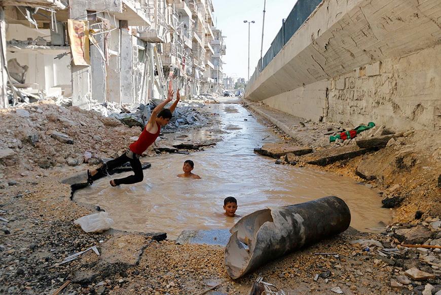 Заполненная водой воронка от бомбы, сброшенной президентскими войсками Сирии. Алеппо, 10 июля 2014. Фото: Hosam Katan / Reuters