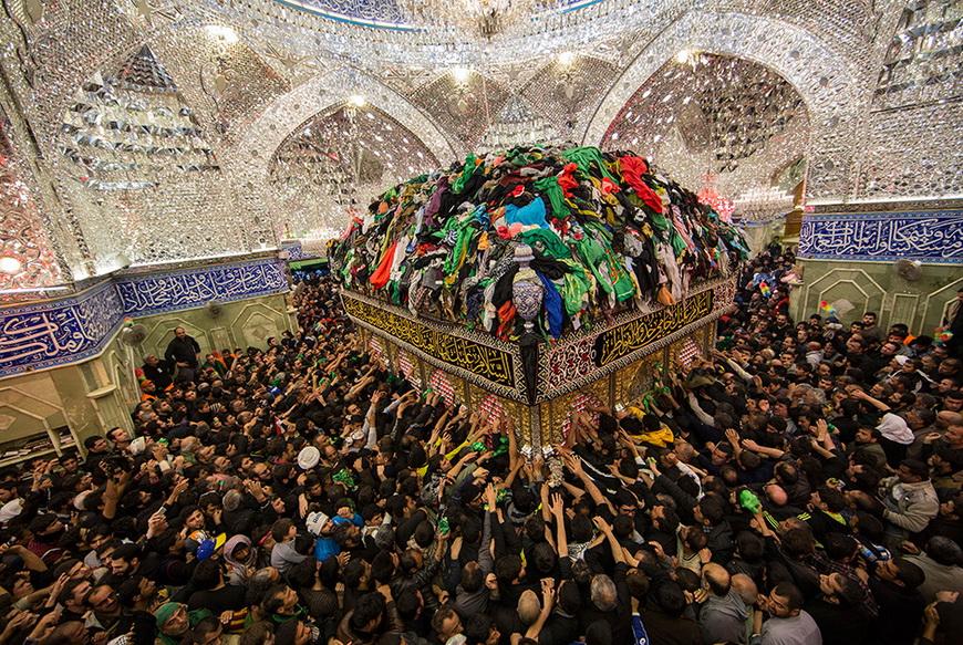 Шиитские паломники-мусульмане пытаются дотянуться до могилы Имама аль-Аббаса. Багдад (Ирак), 13 декабря 2014 года.