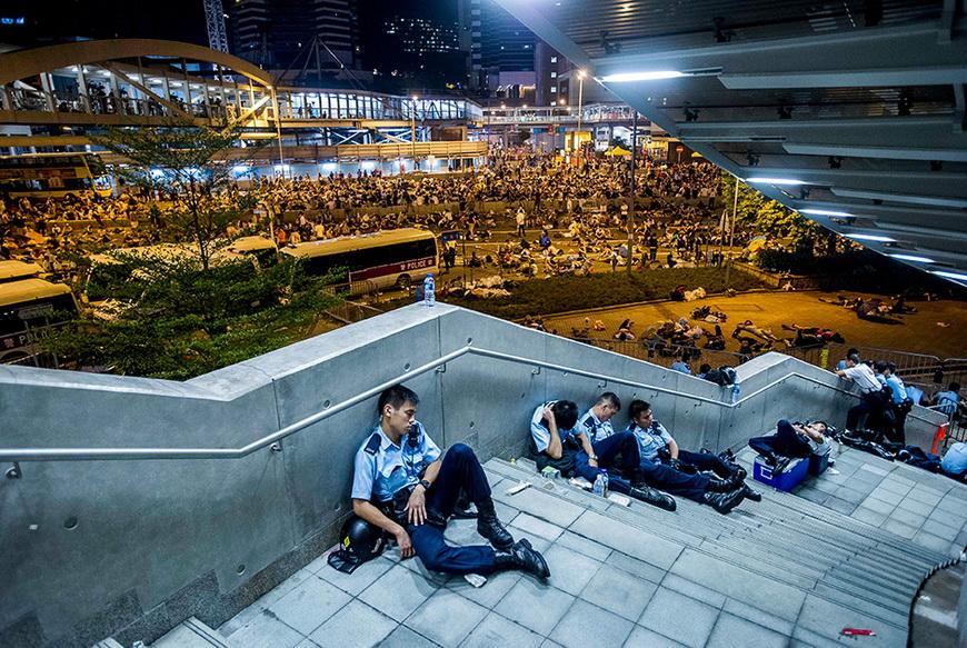 Полицейские отдыхают во время акций протеста против реформы избирательной системы. 29 сентября, Гонконг. Фото: Xaume Olleros / AFP
