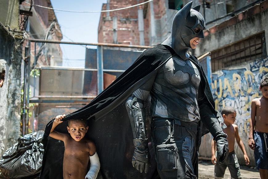 Дети играют с человеком в костюме Бэтмена. 9 января, Рио-де-Жанейро (Бразилия). Фото: Yasuyoshi Chiba / AFP