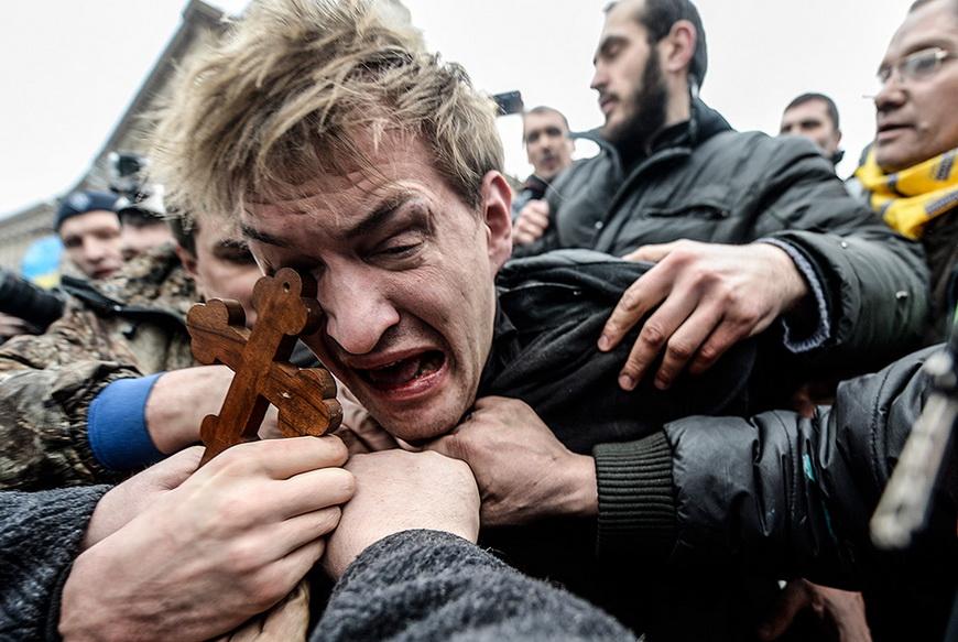 Протестующие избивают предполагаемого снайпера, расстреливавшего людей, находившихся на Майдане. 22 февраля, Киев (Украина). Фото: Bulent Kilic / AFP