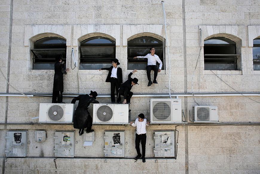 Ортодоксальные евреи взбираются на стену, укрываясь от нападения. Иерусалим (Израиль), 4 августа 2014 года. Фото: Ammar Awad / Reuters