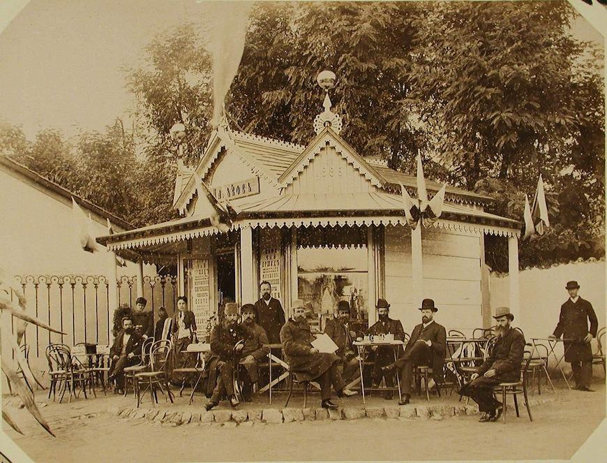 Посетители выставки за столиками у павильона - кафе.