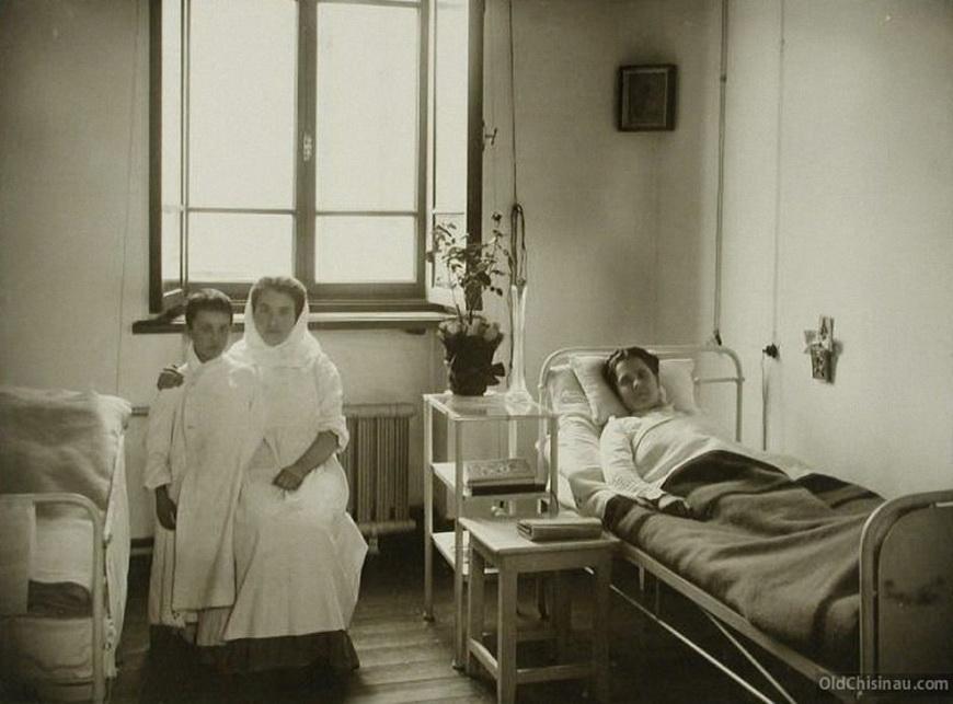 Больная и сестра милосердия с мальчиком в одноместной палате больницы.