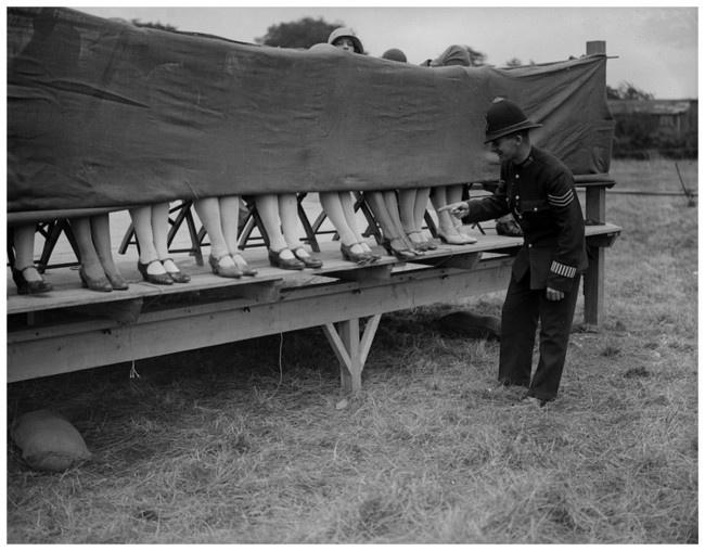 4 Полицейский оценивает лодыжки участниц конкурса красоты в Лондоне. 1930 год.