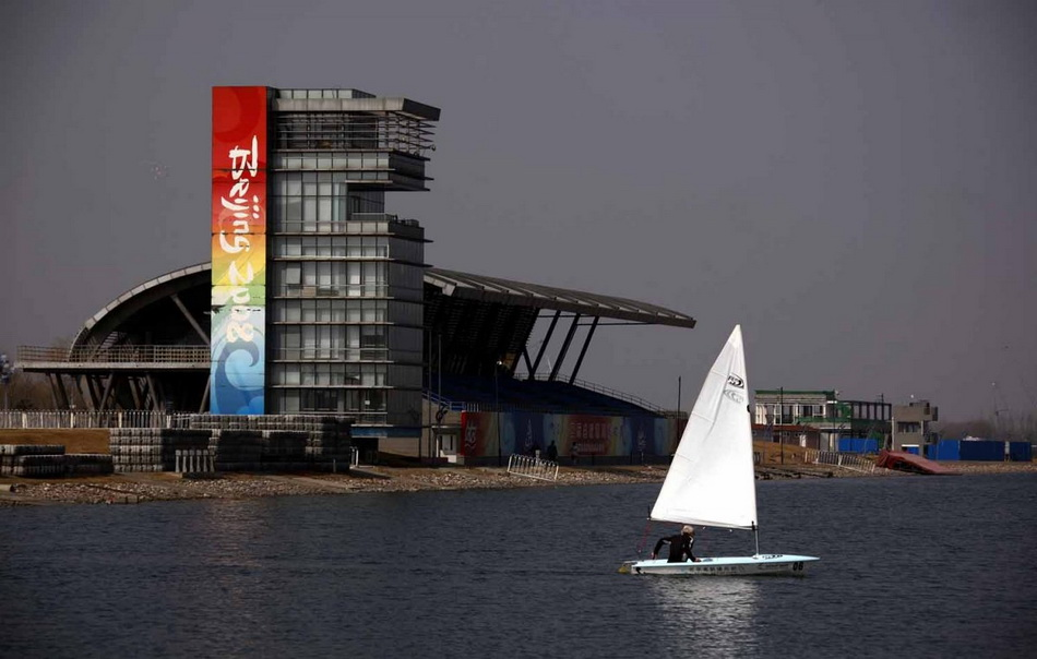 a-boat-sails-past-the-stands-and-observation-tower-from-the-deserted-rowing-facility