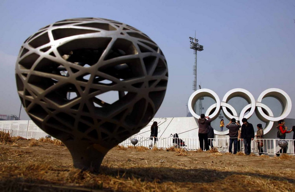 tourists-stand-to-take-pictures-next-to-the-rings-in-a-former-green-area-from-the-olympics